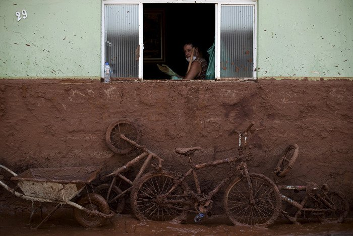 A man works on the cleaning of a house flooded with mud after a dam, owned by Vale SA and BHP Billiton Ltd burst, in Barra Longa, Brazil, November 7, 2015. The death toll from two collapsed dams at a Brazilian mine will surely rise in coming days, a local mayor said on Saturday, as up to 10 residents of the nearest village remain missing in addition to 13 miners. So far one worker has been confirmed dead in what the governor of mineral-rich Minas Gerais described as the state's worst environmental disaster. REUTERS/Ricardo Moraes - RTS5Y8M